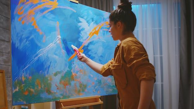Selbstbewusster junger maler mit handtechnik auf neuem gemälde.