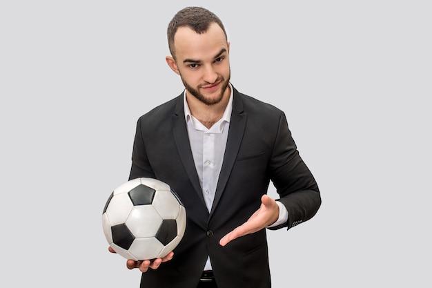 Selbstbewusster junger mann im anzug steht und hält ball zum fußballspielen. er zeigt mit der hand darauf. isoliert auf weißem hintergrund.