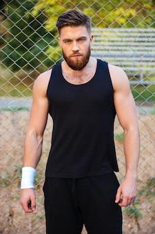 Selbstbewusster junger mann im t-shirt, der draußen steht und nach vorne schaut