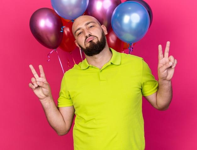 Selbstbewusster junger mann mit gelbem t-shirt, der vor ballons steht und friedensgeste zeigt