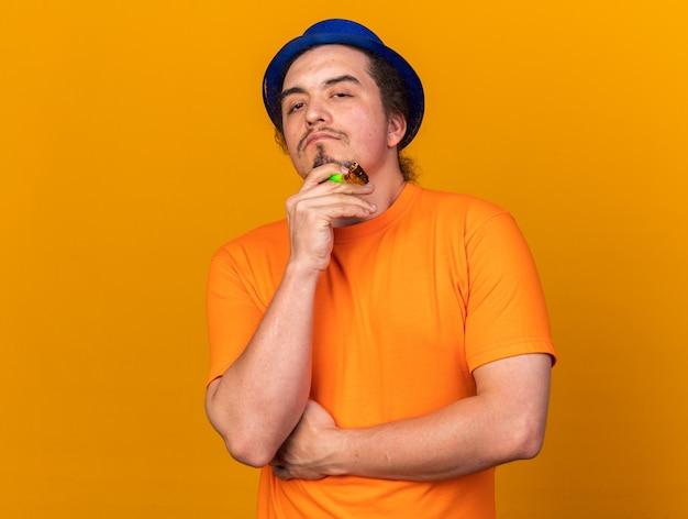 Selbstbewusster junger mann mit partyhut, der partypfeife hält und hand am kinn hält