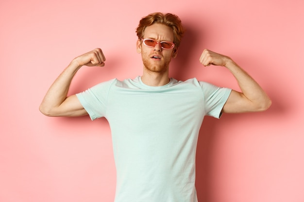 Selbstbewusster junger mann mit roten haaren, der eine sommersonnenbrille und ein t-shirt trägt und einen starken und fitten...