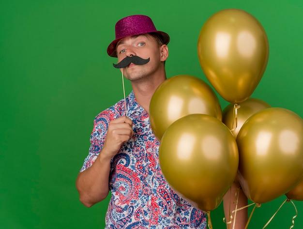 Selbstbewusster junger party-typ, der rosa hut hält, der luftballons hält, die gefälschten schnurrbart auf stock lokalisiert auf grün setzen