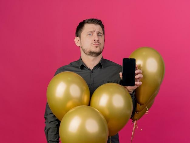 Selbstbewusster junger party-typ, der schwarzes hemd trägt, das unter luftballons steht, die telefon lokalisiert auf rosa halten
