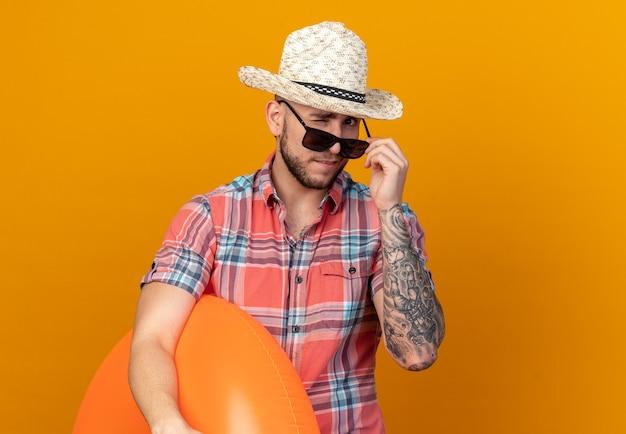 Selbstbewusster junger reisender mit strohhut in sonnenbrille blinzelt mit den augen und hält schwimmring isoliert auf oranger wand mit kopierraum