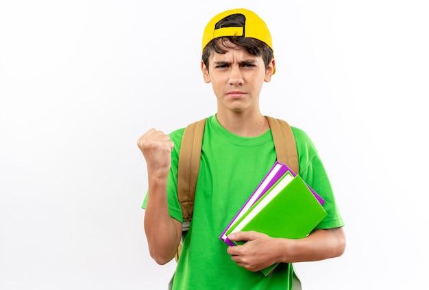 Selbstbewusster junger schuljunge mit rucksack mit mütze mit büchern, die ja-geste zeigen