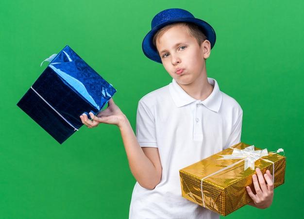 Selbstbewusster junger slawischer junge mit blauem partyhut, der geschenkboxen lokalisiert auf grüner wand mit kopienraum hält