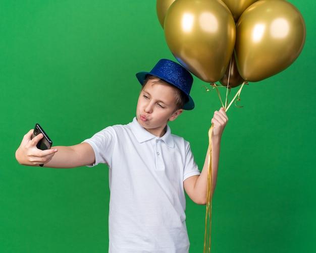 Selbstbewusster junger slawischer junge mit blauem partyhut, der heliumballons hält, die ein selfie am telefon machen, isoliert auf grüner wand mit kopierraum