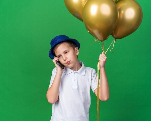 Selbstbewusster junger slawischer junge mit blauem partyhut, der heliumballons hält und am telefon spricht, das seite lokalisiert auf grüner wand mit kopienraum betrachtet