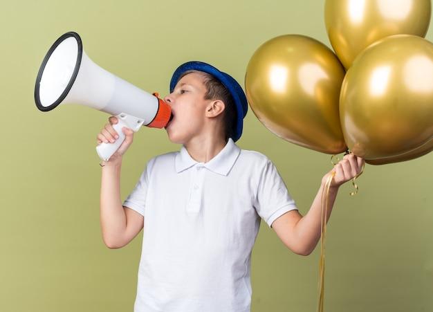 Selbstbewusster junger slawischer junge mit blauem partyhut, der heliumballons hält und in lautsprecher spricht, der seite betrachtet, die auf olivgrüner wand mit kopienraum isoliert ist