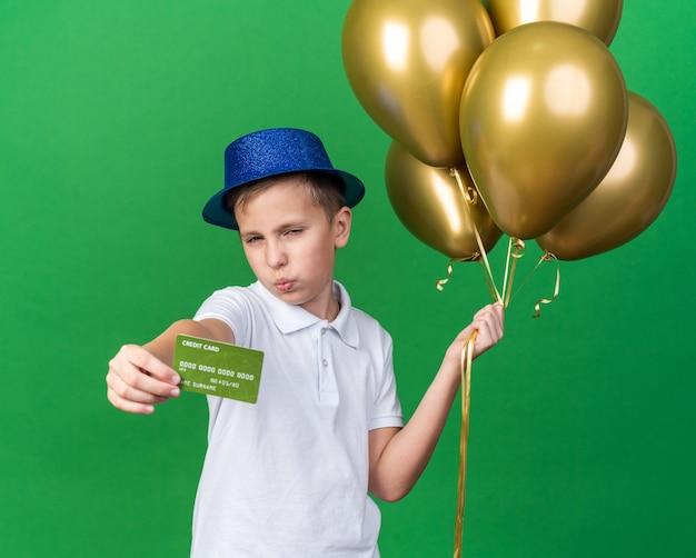 Selbstbewusster junger slawischer junge mit blauem partyhut, der heliumballons und kreditkarte lokalisiert auf grüner wand mit kopienraum hält