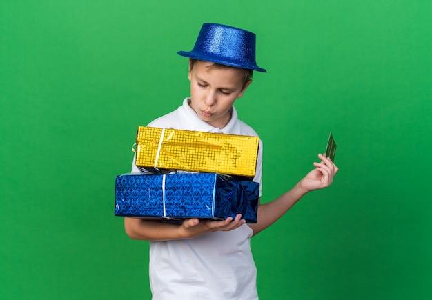 Selbstbewusster junger slawischer junge mit blauem partyhut, der kreditkarte hält und geschenkboxen einzeln auf grüner wand mit kopienraum betrachtet