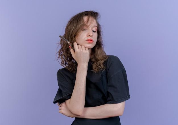 Selbstbewusster junger slawischer weiblicher friseur, der uniform hält, die schere hält, die unten hand unter kinn lokalisiert auf lila hintergrund mit kopienraum schaut