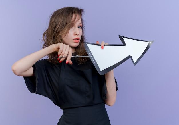 Selbstbewusster junger slawischer weiblicher friseur, der uniform hält, die schere und pfeilmarkierung hält, die zur seite zeigt, die versucht, pfeilmarkierung lokalisiert auf lila hintergrund zu schneiden