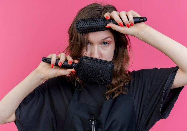 Selbstbewusster junger slawischer weiblicher friseur, der uniform trägt, die kamera zwischen kämmen berührt, die gesicht mit ihnen lokalisiert auf rosa hintergrund berühren