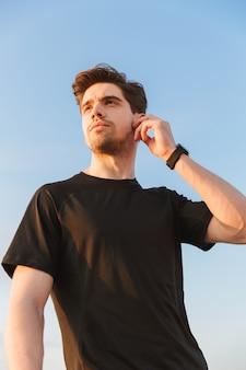 Selbstbewusster junger sportler im schwarzen t-shirt