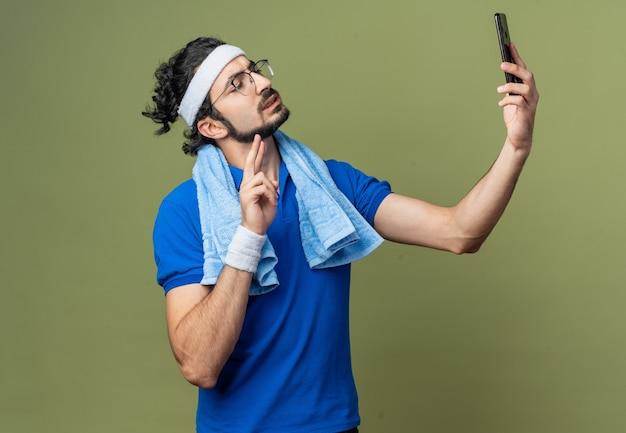Selbstbewusster junger sportlicher mann, der stirnband mit armband und handtuch auf der schulter trägt, macht ein selfie