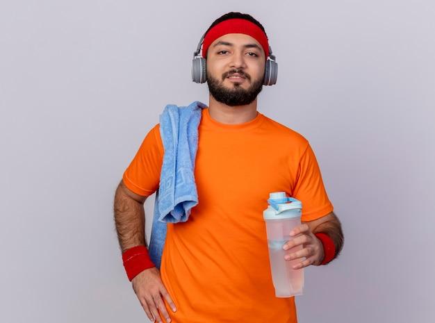 Selbstbewusster junger sportlicher mann, der stirnband und armband mit kopfhörern trägt, die hand auf hüfte setzen