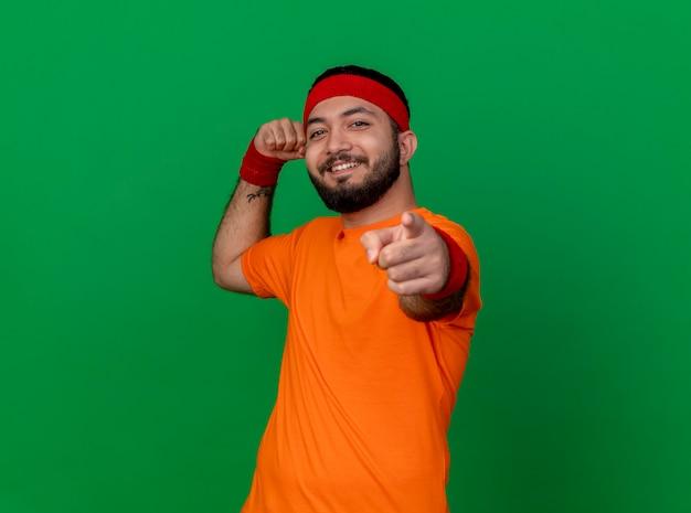 Selbstbewusster junger sportlicher mann, der stirnband und armband trägt und starke geste zeigt