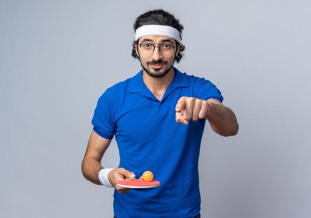 Selbstbewusster junger sportlicher mann mit stirnband mit armband, das einen tischtennisball an den schlägerpunkten vorne hält