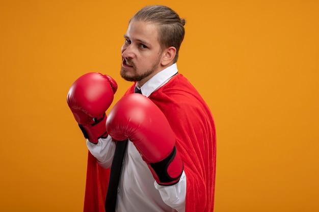 Selbstbewusster junger superheld, der krawatte und boxhandschuhe trägt, die in der kampfhaltung stehen, lokalisiert auf orange hintergrund mit kopienraum