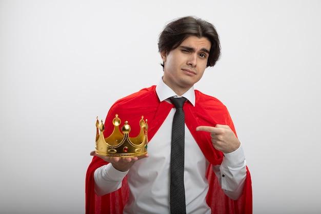 Selbstbewusster junger superheld, der krawattenhalter trägt und auf krone zeigt