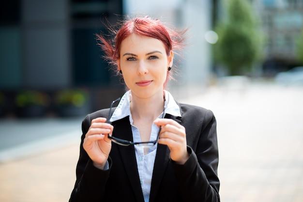 Selbstbewusster junger weiblicher manager im freien in einer modernen städtischen umgebung, die ihre brille hält