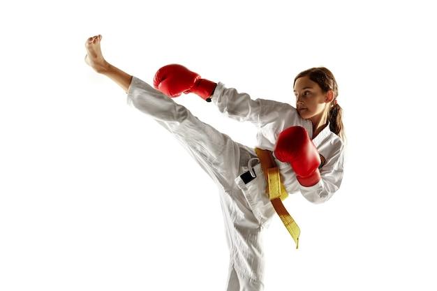 Selbstbewusster junior im kimono, der nahkampf und kampfkunst praktiziert. junge kämpferin mit training des gelben gürtels auf weißer wand. konzept des gesunden lebensstils, des sports, der aktion.