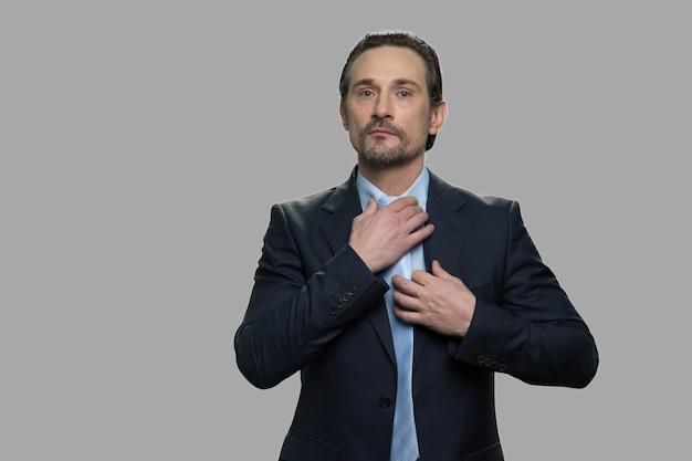 Selbstbewusster kaukasischer geschäftsmann, der sich auf geschäftstreffen vorbereitet. hübscher mann mittleren alters, der seine krawatte anpasst. auf grauem hintergrund isoliert.