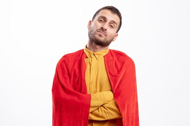 Selbstbewusster kaukasischer superheldenmann mit rotem umhang steht mit verschränkten armen lokalisiert auf weißer wand mit kopienraum