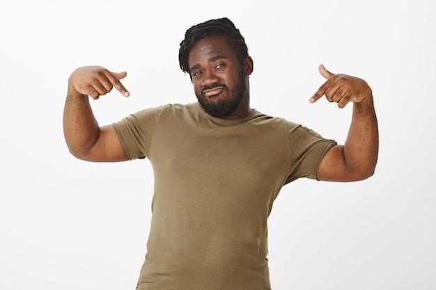 Selbstbewusster kerl in einem braunen t-shirt, das gegen die weiße wand aufwirft