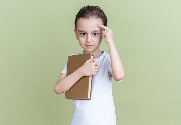 Selbstbewusster kleiner junge, der ein buch hält und eine denkgeste macht