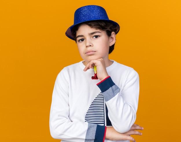 Selbstbewusster kleiner junge mit blauem partyhut, der eine partypfeife hält und die hand unter das kinn legt, isoliert auf oranger wand