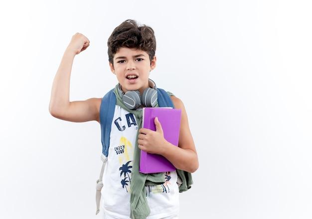 Selbstbewusster kleiner schuljunge, der rucksack und kopfhörer trägt, buch hält und starke geste tut