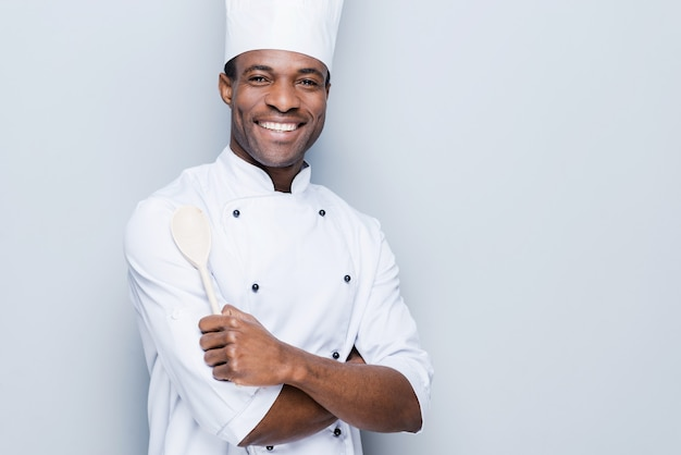 Selbstbewusster koch. fröhlicher junger afrikanischer koch in weißer uniform, der die arme verschränkt und lächelt