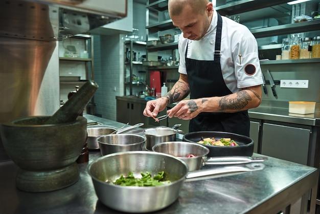 Selbstbewusster koch mit mehreren tattoos auf den armen garniert italienische pasta in einer restaurantküche
