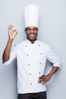 Selbstbewusster koch. selbstbewusster junger afrikanischer koch in weißer uniform, der ok-zeichen gestikuliert und lächelt