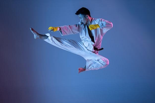 Selbstbewusster koreanischer mann im kimono, der hand-hand-kampfkünste übt