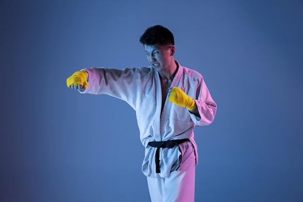 Selbstbewusster koreanischer mann im kimono, der hand-zu-hand-kampfkünste praktiziert