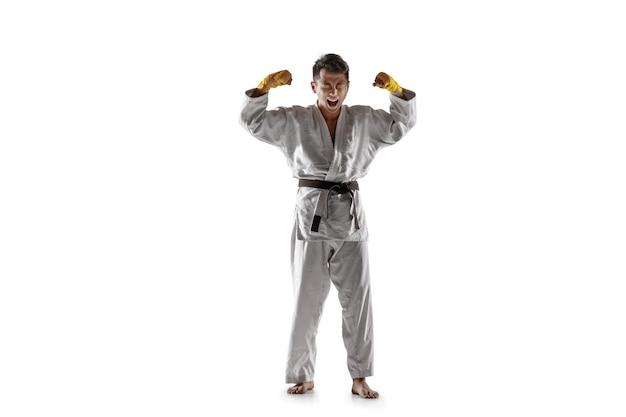 Selbstbewusster koreanischer mann im kimono, der nahkampf, kampfkünste praktiziert. junger männlicher kämpfer mit schwarzem gürtel feiert sieg isoliert auf weißer wand. konzept des gesunden lebensstils, sport.