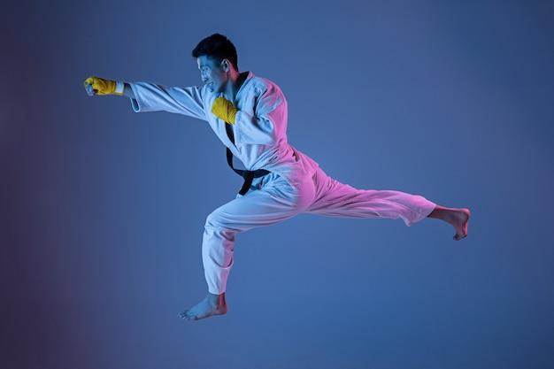 Selbstbewusster koreanischer mann im kimono, der nahkampf, kampfkünste praktiziert. junger männlicher kämpfer mit schwarzem gürteltraining auf steigungshintergrund im neonlicht. konzept des gesunden lebensstils, sport.