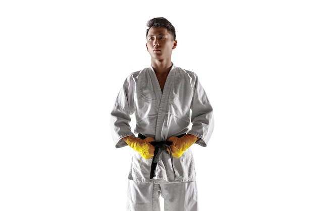 Selbstbewusster koreanischer mann im kimono, der nahkampf, kampfkünste praktiziert. junger männlicher kämpfer mit schwarzem gürteltraining isoliert auf weißem studiohintergrund. konzept des gesunden lebensstils, sport.