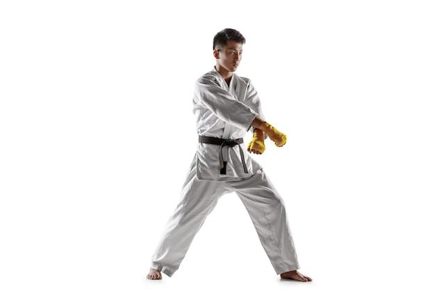 Selbstbewusster koreanischer mann im kimono, der nahkampf, kampfkünste praktiziert. junger männlicher kämpfer mit schwarzem gürteltraining isoliert auf weißer wand. konzept des gesunden lebensstils, sport.