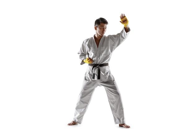 Selbstbewusster koreanischer mann im kimono, der nahkampf, kampfkunst praktiziert