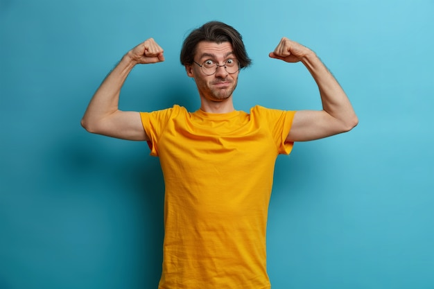 Selbstbewusster, kraftvoller mann hebt die arme und zeigt muskeln, zeigt das ergebnis eines regelmäßigen trainings, trägt ein gelbes t-shirt und eine brille, führt einen aktiven, gesunden lebensstil und ist sehr stark