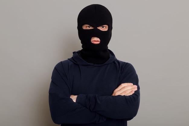 Selbstbewusster krimineller mann, der isoliert auf einer grauen oberfläche aufwirft