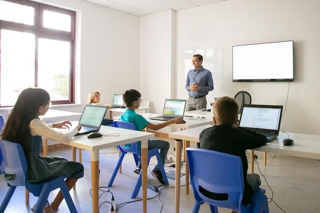 Selbstbewusster lehrer, der den schülern den unterricht erklärt