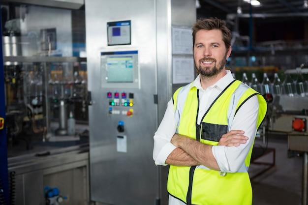 Selbstbewusster männlicher arbeiter, der in der fabrik steht