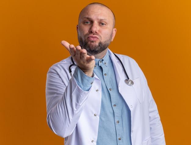 Selbstbewusster männlicher arzt mittleren alters, der ein medizinisches gewand und ein stethoskop trägt und einen schlagkuss sendet