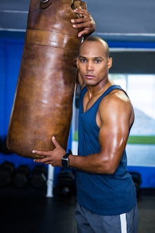 Selbstbewusster männlicher athlet durch boxsack